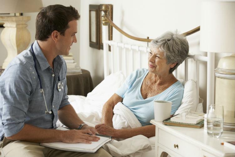Elderly woman in her bed speaking to her doctor