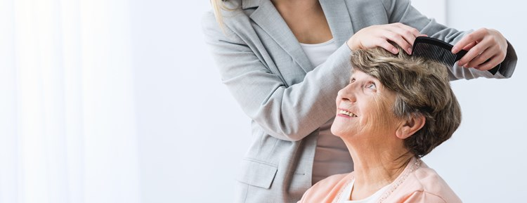Caregiver brushing elderly mothers hair