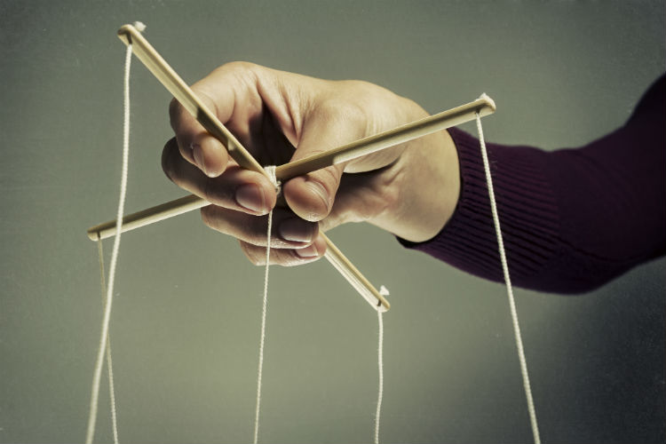 A hand holding up puppet strings symbolizing manipulation