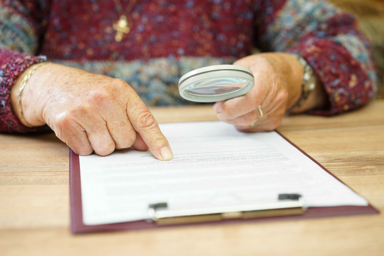 Woman looking at a document with a magnifying glass