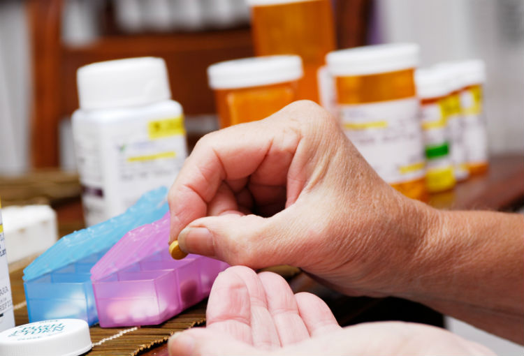 Person organizing medications with pill boxes