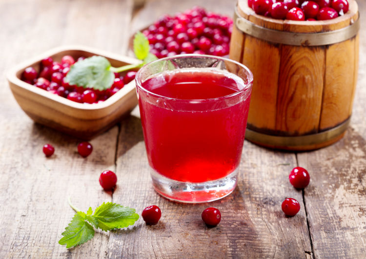 A glass of cranberry juice with bowls of cranberries on a table