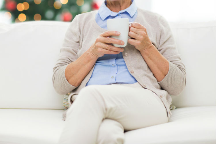 Senior woman with a cup of tea at home alone with christmas tree background