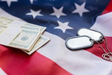 A pile of money and a pair of dog tags laying on top of an american flag