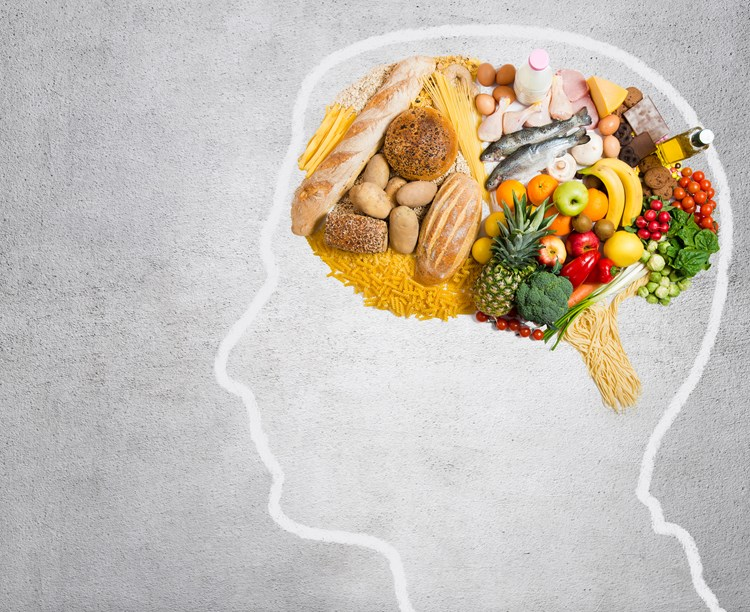 An outline of a human head with a brain shaped out of healthy food inside