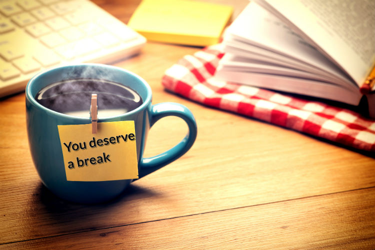 "A coffee cup on a table with a sticky note attached reading ""you deserve a break"""